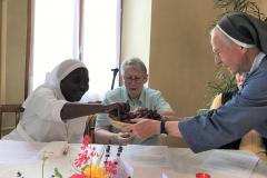 Sr Chantal tendue vers Sr Marie-Chantal pour offrir un grain de raisin